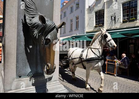 Belgique, Flandre occidentale, Bruges, partie sud du centre historique classé au Patrimoine Mondial de l'UNESCO, Wijngaardplein square, en calèche en passant en face de la fontaine de chevaux Banque D'Images