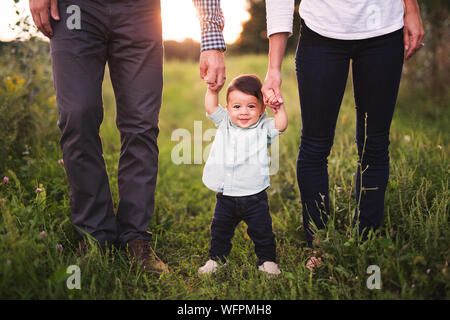 Portrait Of Cute Baby Boy Holding Parents mains tandis que l'article sur l'herbe Banque D'Images