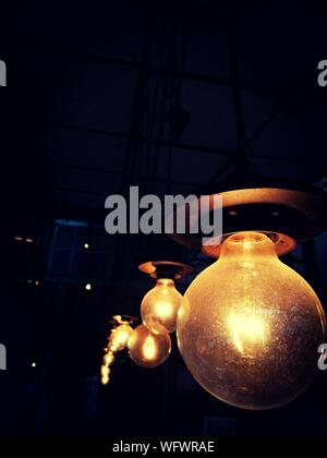 Low Angle View Of Illuminated Ampoules suspendues dans Darkroom Banque D'Images