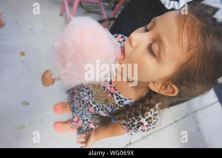 High Angle View of Girl Eating Cotton Candy Banque D'Images