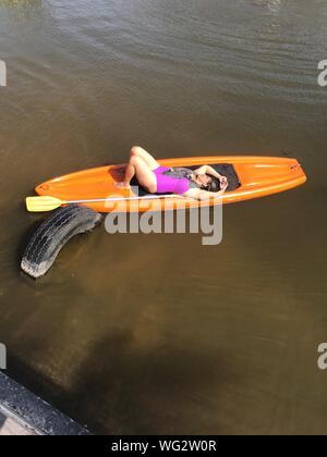 La longueur totale de la femme couchée sur le lac en kayak