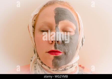 Close-up of Young Woman avec masque du visage de boue contre fond blanc Banque D'Images