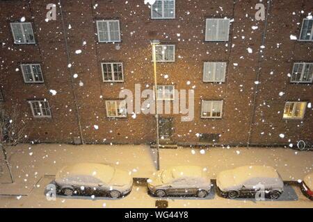 Voitures garées en face d'un immeuble résidentiel en hiver Banque D'Images