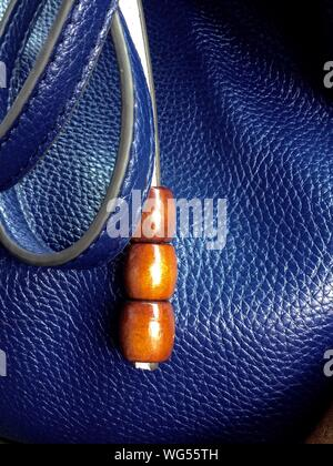 Close-up de perles brunes sur la sangle de sac bleu