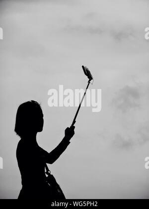 Prendre Femme Silhouette contre le ciel Selfies Banque D'Images