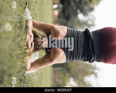 Vue arrière du Woman Practicing Wavecrest On Grassy Field Banque D'Images