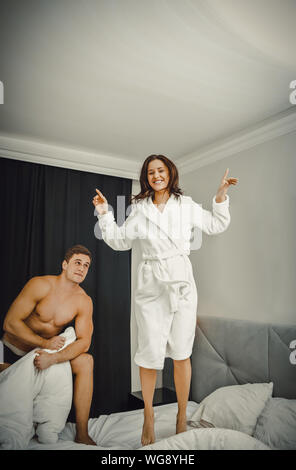 Shirtless Man Looking At Cheerful Woman Jumping on Bed At Home Banque D'Images