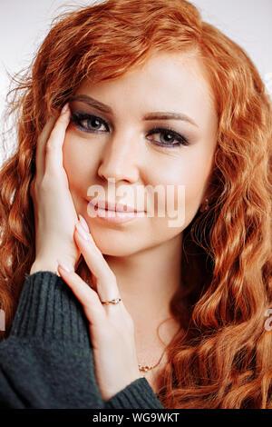 Belle jeune femme à nettoyer la peau parfaite. Bonne recherche mignon femelle toucher doucement le visage avec la paume et être souriant, satisfait de résultat de fac