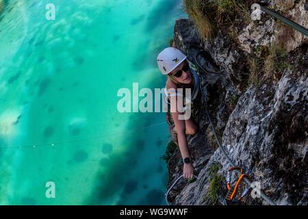 Une femme monte sur la via ferrata au-dessus du Lac de la Rosière près de la station de ski française de Courchevel dans les Alpes pendant l'été. Banque D'Images