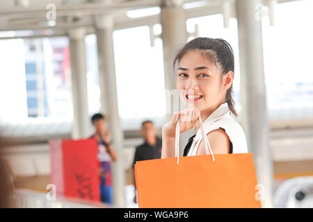 Side View Portrait Of Smiling Young Woman Holding Shopping Bags In Covered Bridge Banque D'Images