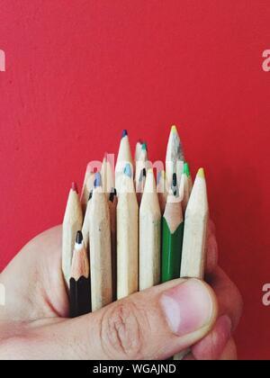 Cropped Hand Holding Crayons de couleur contre fond rouge Banque D'Images