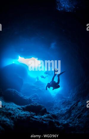 Low Angle View Of Scuba Divers Natation Dans Cave Banque D'Images