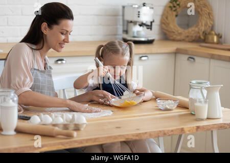 Petite fille et sa mère cuisiniers pie together in kitchen Banque D'Images