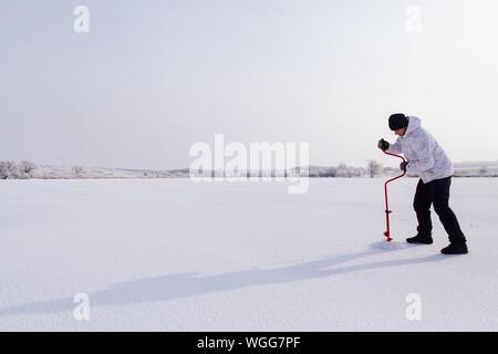 Toute la longueur de l'Homme debout avec mât sur la neige contre le ciel Banque D'Images