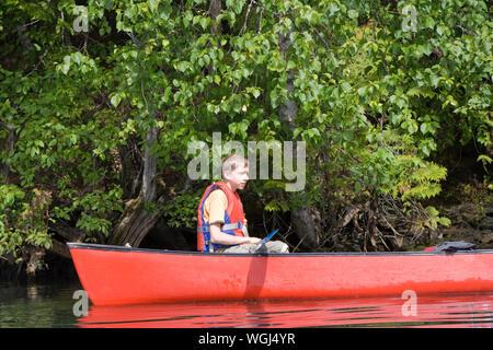 Vue latérale du Teenage Boy Wearing Gilet de canoë sur le lac Banque D'Images