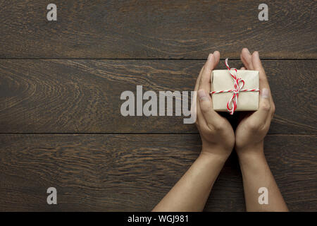 Portrait Of Hands Holding Gift On Table Banque D'Images