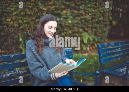 Jeune femme dans un chandail de lire un livre, assis sur le banc dans le parc. Temps d'automne.