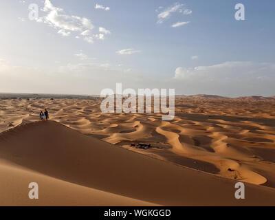 Portrait d'amis sur Dune de sable contre le ciel Banque D'Images