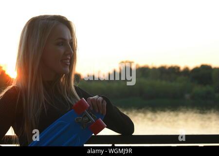 Cheveux blonds femme posant avec son scateboard en souriant avant de le coucher du soleil sur le bord de mer avec beaucoup de copyspace Banque D'Images