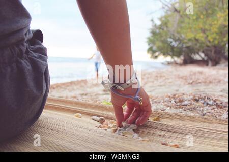 La section basse de Femme avec des coquillages sur la plage Banque D'Images