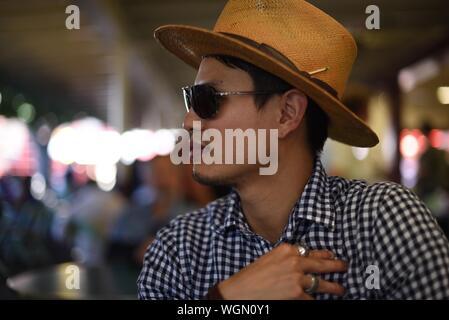 Portrait d'un homme portant des lunettes de soleil et chapeau Banque D'Images