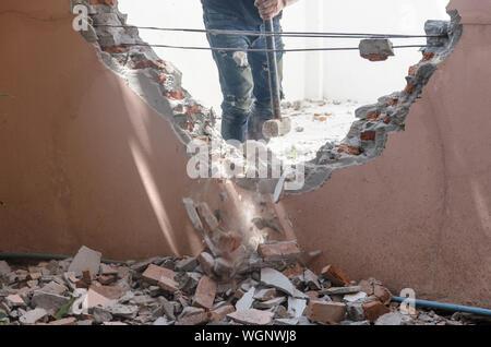 Au milieu du travailleur de la Construction à démolir mur avec Sledgehammer Banque D'Images