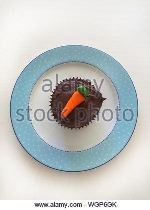 Vue directement au-dessus de carotte frais servi dans Cupcake Plaque sur fond blanc