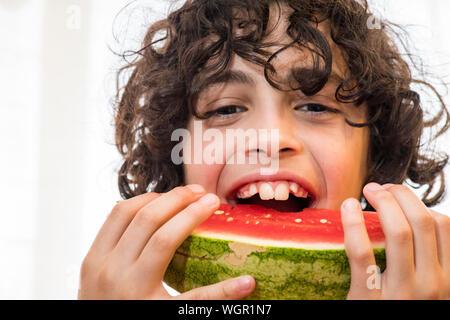 Portrait Of Boy Eating Watermelon contre mur Banque D'Images