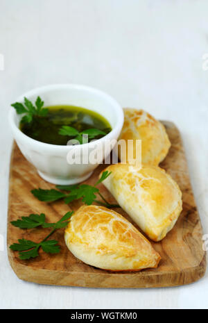 Empanadas avec sauce Chimichurri sur conseil de cuisine en bois Banque D'Images