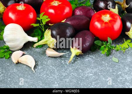 Les tomates, aubergines et l'ail sur stone texture background. Banque D'Images