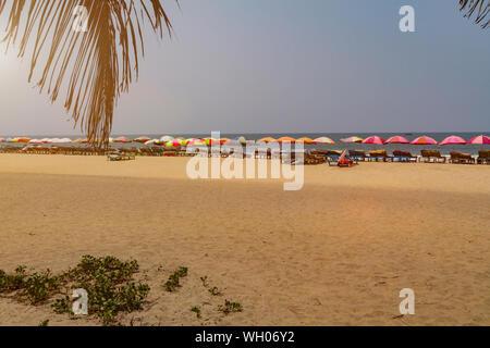 Rangée de chaises longues avec parasols colorés sur la plage de Goa, en Inde. Long Shot, tonique du soleil. Maison de vacances tamplate. Banque D'Images