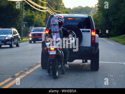 Storrs, CT USA. Aug 2019. Jeune motocycliste à une intersection avec un skateboard attaché à sac à dos à la façon d'un skatepark. Banque D'Images