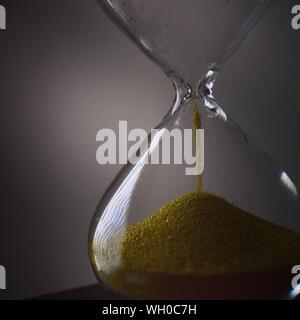 Close-up de Hourglass sur table contre fond gris Banque D'Images