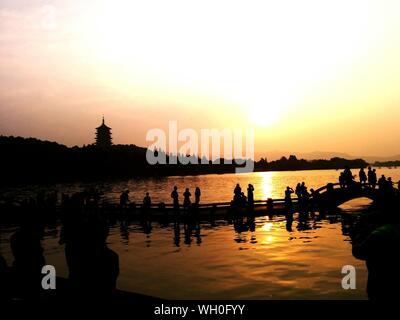 Les gens Silhouette debout sur passerelle sur le lac de l'Ouest contre le ciel au coucher du soleil Banque D'Images