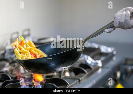 Chef, c'est en remuant les légumes dans le wok Banque D'Images