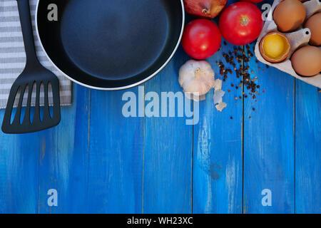 Le petit-déjeuner ensemble. Poêle, des tomates, des œufs crus, oignons, ail, épices. Focus sélectif. Copier l'espace. Vue d'en haut. Bleu sur fond de bois. Close-up. Banque D'Images