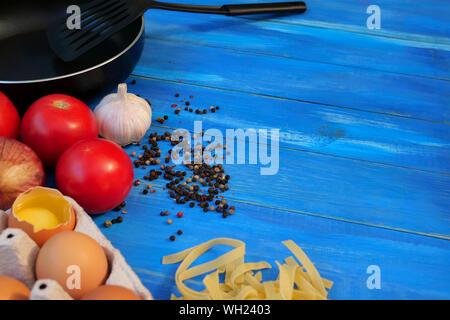 Le petit-déjeuner ensemble. Poêle, des tomates, des œufs crus, oignons, ail, épices, pâtes sèches. Focus sélectif. Copier l'espace. Bleu sur fond de bois. Close-up. Banque D'Images