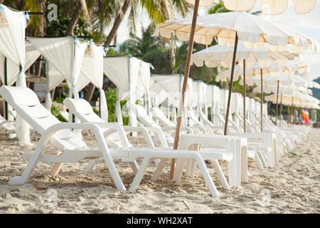 Des chaises longues et des tables vides At Beach Banque D'Images
