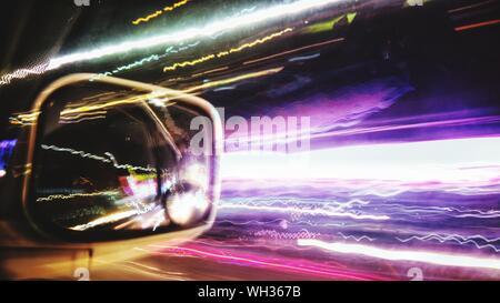 Des sentiers de lumière éclairé réfléchissant sur voiture rétroviseur Banque D'Images