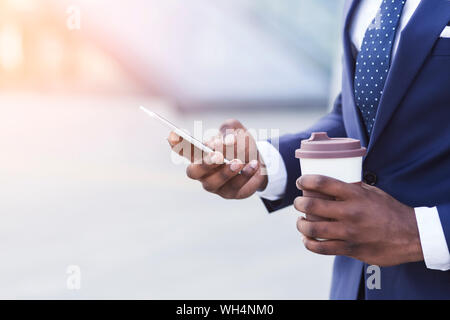 Méconnaissable Businessman Using Phone Holding Coffee Cup in Urban Area Banque D'Images