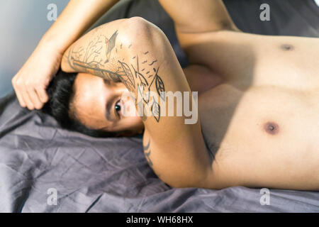 Portrait Of Shirtless Man avec bras tatoués Lying On Bed At Home Banque D'Images