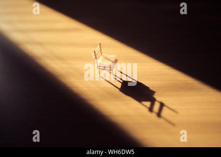 Petite chaise sur un plancher en bois dans une pièce sombre avec un flux de lumière vive dans un coin. Banque D'Images