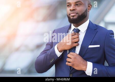Jeune black Businessman Adjusting Necktie en zone urbaine Banque D'Images