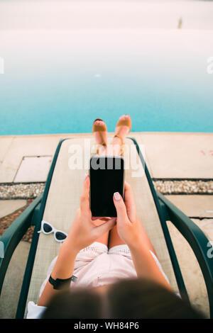 De soleil femme en fauteuil par la piscine et l'utilisation de téléphone mobile Banque D'Images