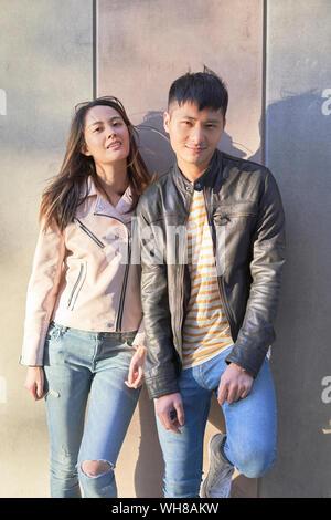 Portrait de couple wearing leather jackets leaning against wall