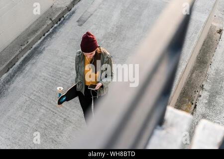 Jeune femme élégante avec skateboard et téléphone cellulaire sur parking