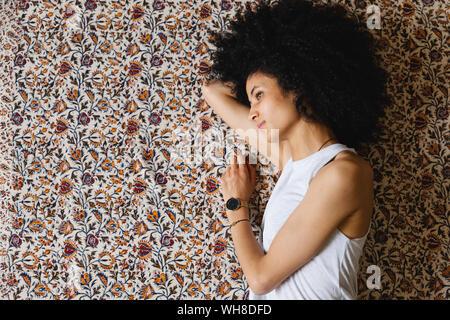 Jeune femme couchée sur le côté sur le tapis
