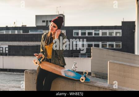 Jeune femme élégante avec du skateboard, des écouteurs et un téléphone cellulaire sur parking Banque D'Images