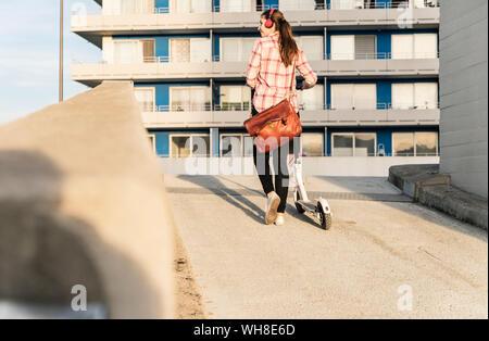 Jeune femme avec un casque scooter électrique poussant sur parking Banque D'Images