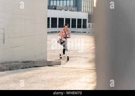 Jeune femme avec un casque équitation scooter électrique sur parking Banque D'Images